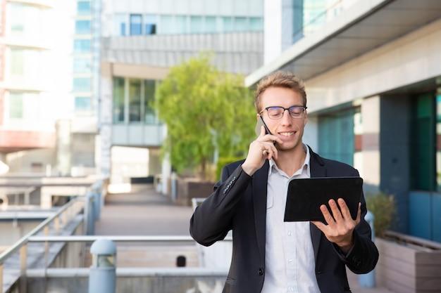 Vrolijke manager die op telefoon spreekt Gratis Foto