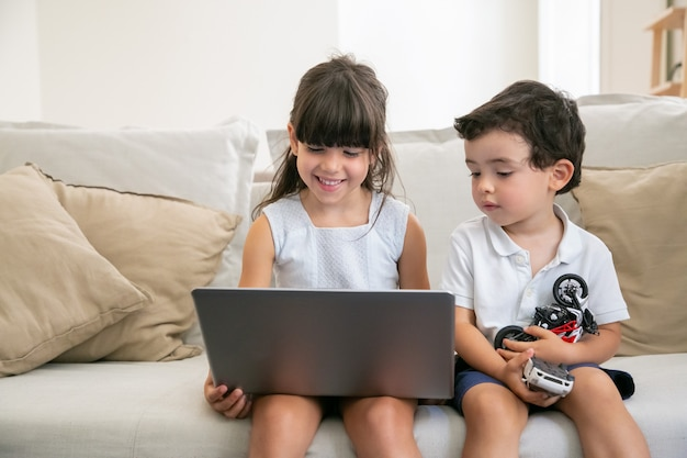 Vrolijke meisje en haar broertje zittend op de bank thuis, met behulp van laptop voor video-oproep, online chat, video of film kijken. Gratis Foto
