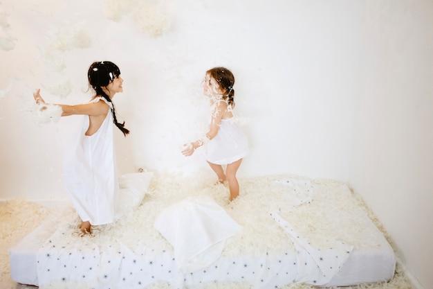 Vrolijke meisjes die veren op matras werpen Gratis Foto