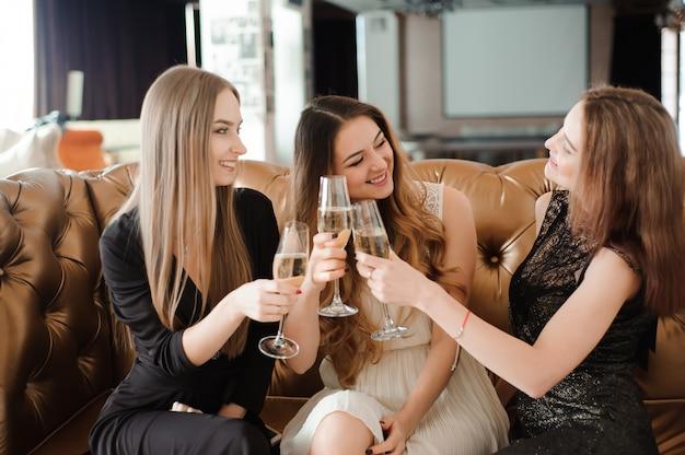 Vrolijke meisjes rammelende glazen champagne op het feest Premium Foto