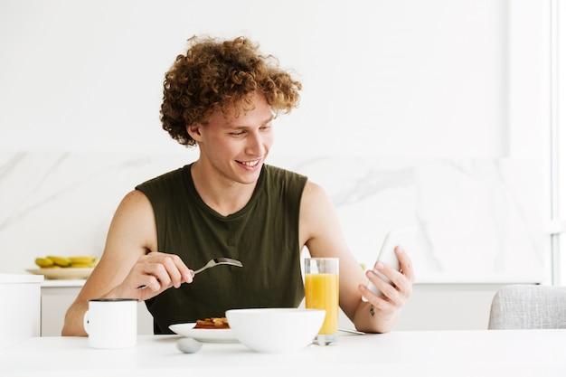 Vrolijke mens gebruikend mobiele telefoon en etend gebakjes Gratis Foto