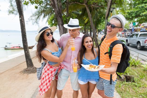 Vrolijke mensen op zee groep vrienden houden van aziatische street food walk Premium Foto