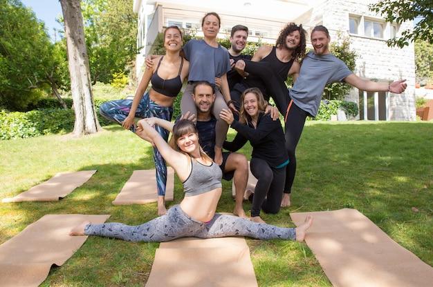 Vrolijke mensen van yogateam die in openlucht stellen Gratis Foto
