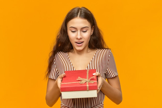 Vrolijke modieuze jonge vrouw die de mooie gestreepte doos van de kledingsholding draagt Gratis Foto
