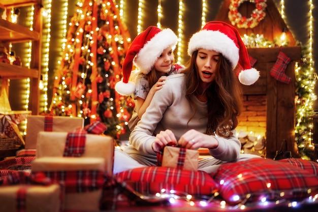 Vrolijke moeder en haar schattige dochter meisje geschenken uitwisselen. ouder en kleine kinderen die pret hebben dichtbij boom binnen. liefdevolle familie met presenteert in kerst kamer. Premium Foto