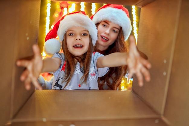 Vrolijke moeder en haar schattige dochter meisje openen een kerstcadeau Premium Foto