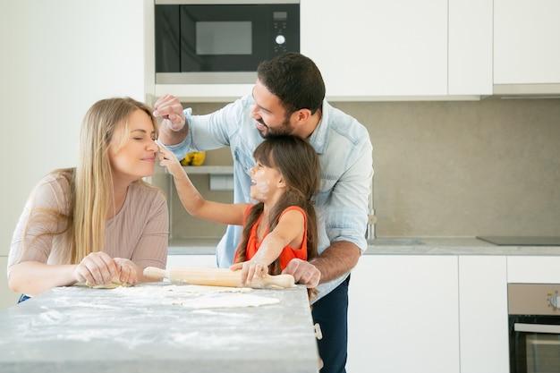 Vrolijke moeder, vader en meisje kleuren gezichten met bloempoeder tijdens het samen bakken. Gratis Foto