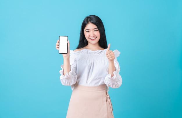 Vrolijke mooie aziatische smartphone van de vrouwenholding met shows zoals teken Premium Foto
