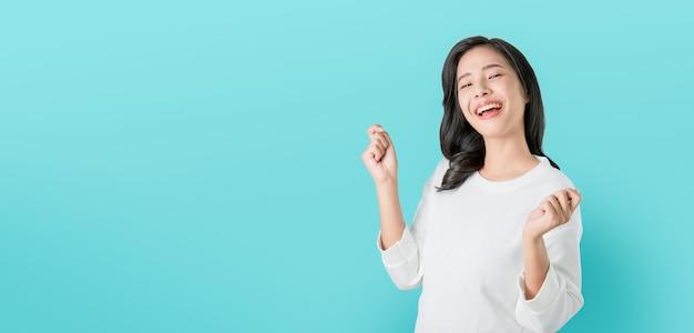 Vrolijke mooie aziatische vrouw in casual wit t-shirt en blij gezicht glimlachen op blauwe achtergrond Premium Foto