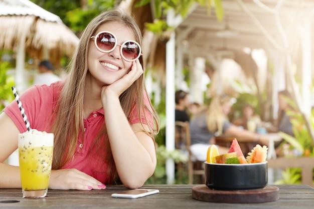 Vrolijke mooie dame stijlvolle ronde zonnebril dragen, zittend aan een bar met cocktail, fruit en mobiele telefoon op houten tafel, leunend op haar elleboog en kijken met gelukkige vrolijke glimlach, genieten van vakanties Gratis Foto