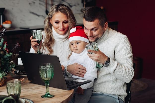 Vrolijke, mooie familie met een baby die drankjes grootbrengt tijdens het communiceren via laptop vanuit huis. Gratis Foto