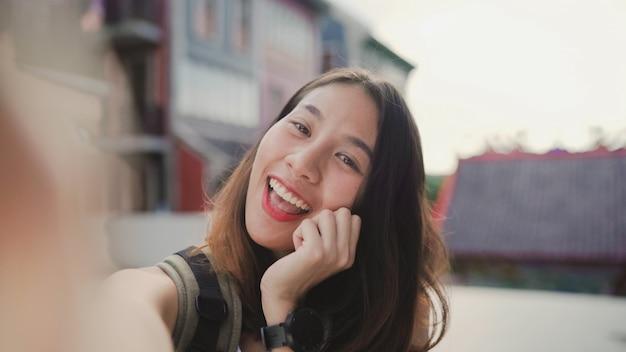Vrolijke mooie jonge aziatische backpacker blogger vrouw met behulp van smartphone selfie te nemen Gratis Foto