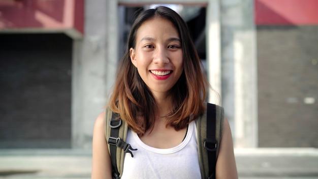 Vrolijke mooie jonge aziatische backpackervrouw die het gelukkige glimlachen aan camera voelen Gratis Foto