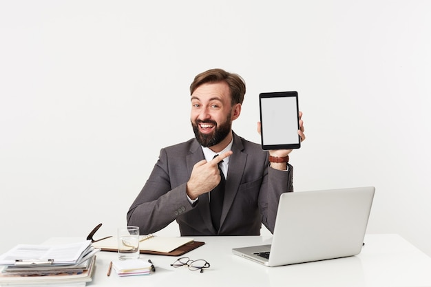 Vrolijke mooie jonge bebaarde brunette man met trendy kapsel wijzend met wijsvinger naar tablet-pc in zijn hand en breed glimlachend, gekleed in grijs pak zittend aan tafel over witte muur Gratis Foto