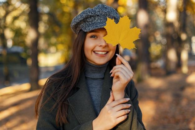 Vrolijke mooie jonge lachende vrouw met een hoed in een modieuze jas bedekt haar gezicht met een gele herfstblad in het park. geniet van het herfstweer. Premium Foto
