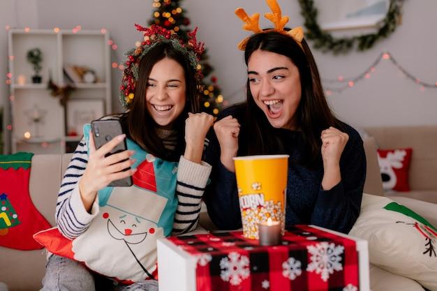 Vrolijke mooie jonge meisjes houden vuisten en kijken naar telefoon zittend op fauteuils en genieten van kersttijd thuis Gratis Foto