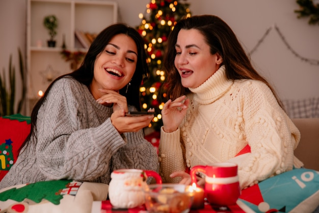 Vrolijke mooie jonge meisjes kijken naar telefoon zittend op fauteuils en genieten van kersttijd thuis Gratis Foto