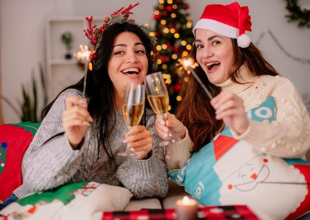 Vrolijke mooie jonge meisjes met kerstmuts gerinkel glazen champagne en houden wonderkaarsen zittend op fauteuils en genieten van kersttijd thuis Gratis Foto