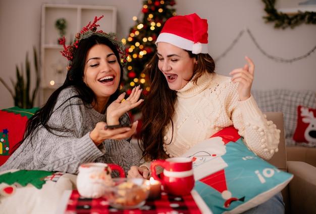 Vrolijke mooie jonge meisjes met kerstmuts kijken naar telefoon zittend op fauteuils en genieten van kersttijd thuis Gratis Foto