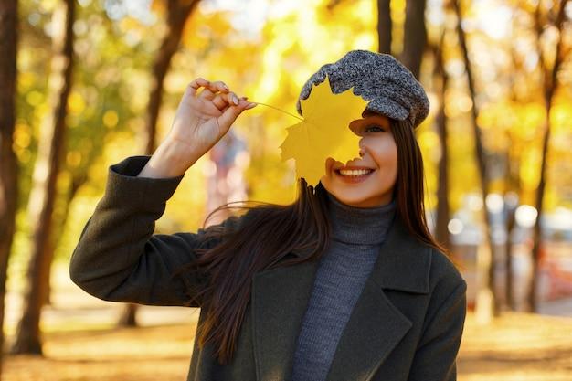 Vrolijke mooie jonge vrouw met een glimlach in modieuze vintage kleding met een jas en hoed met gele herfstblad wandelen in het park Premium Foto