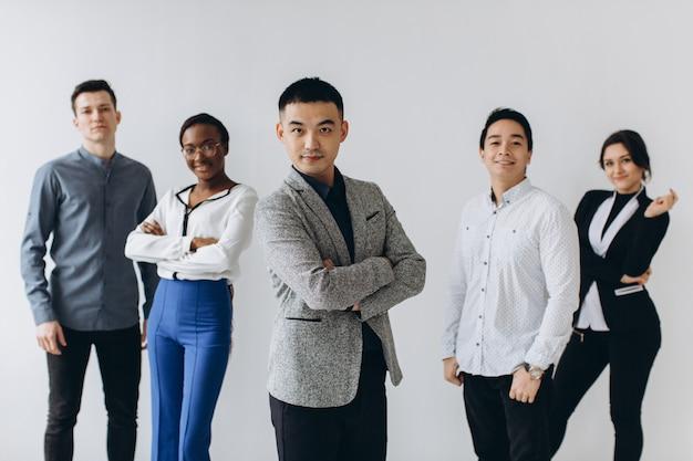Vrolijke multiraciale professionele mensen uit het bedrijfsleven lachen samen staan in de rij in de buurt van muur, gelukkig diverse jonge werknemers studenten groep, corporate team van personeel plezier, human resource concept Premium Foto
