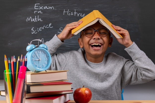 Vrolijke nadenkende schooljongen met kantoorbehoeftenlevering op klaslokaalbureau Premium Foto