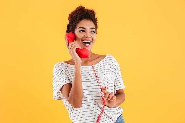 Vrolijke op rode telefoon spreken en dame die opzij kijken Gratis Foto
