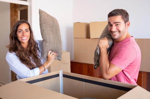Vrolijke opgewonden jonge man en vrouw die kussens van een open kartonnen doos uitstappen, genieten van het verplaatsen en uitpakken van dingen Gratis Foto