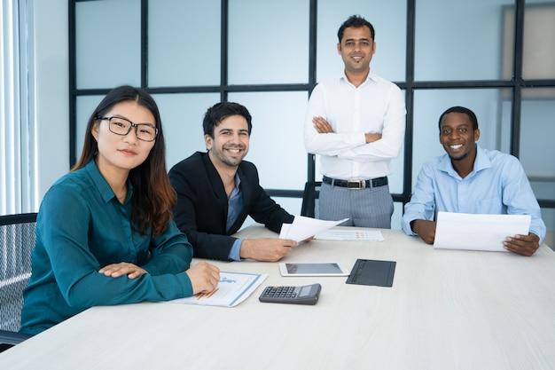 Vrolijke optimistische verkoopmanagers die rapport analyseren en camera in raadskamer bekijken. Gratis Foto