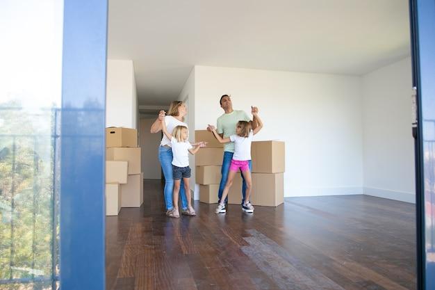 Vrolijke ouders en dochters die dansen en plezier hebben in de buurt van hopen dozen terwijl ze naar een nieuwe flat verhuizen Gratis Foto