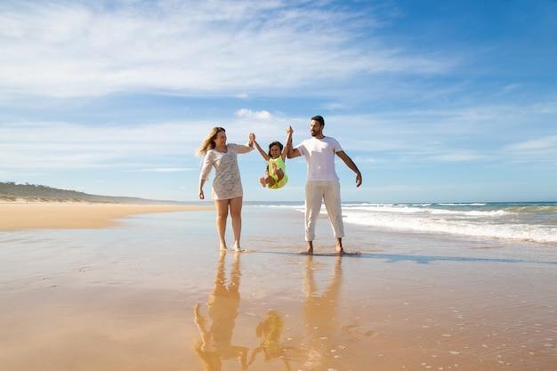 Vrolijke ouders en meisje genieten van wandelen en activiteiten op het strand, kind ouders hand in hand, springen en benen overgeven Gratis Foto