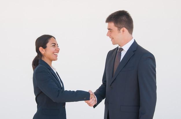 Vrolijke partners die handen schudden Gratis Foto