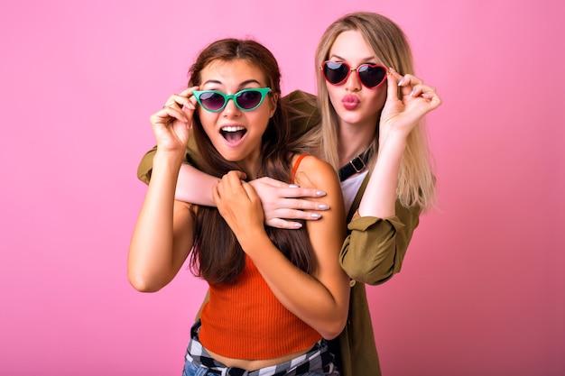 Vrolijke positieve indoor portret van twee grappige blonde en brunette vrouw knuffels en op zoek naar elkaar Gratis Foto
