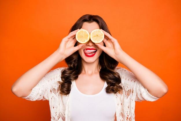 Vrolijke positieve schattige mooie mooie prachtige vrouw likt haar bovenlip op zoek naar twee citroenen als een verrekijker. Premium Foto