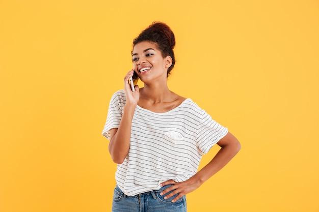Vrolijke positieve vrouw die op geïsoleerde telefoon spreekt Gratis Foto