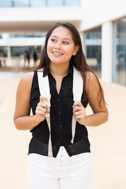 Vrolijke positieve vrouwelijke toerist die buiten loopt Gratis Foto
