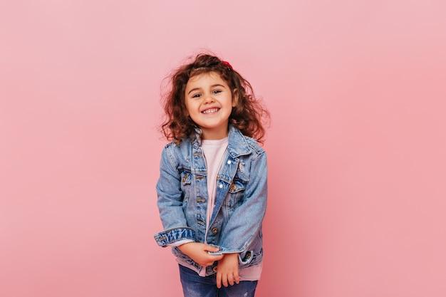 Vrolijke preteen jongen met krullend haar camera lachen. studio shot van onbezorgd meisje geïsoleerd op roze achtergrond. Gratis Foto