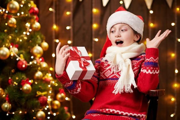 Vrolijke santa helper meisje met geschenkdoos zit binnen in de buurt van dec Premium Foto