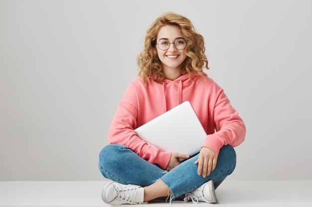 Vrolijke slimme studente zittend op de vloer met laptop Gratis Foto
