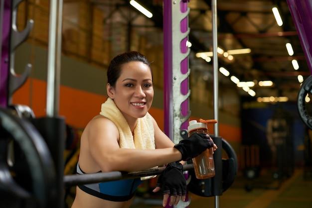 Vrolijke sportvrouw die bij camera bij de smith-machine in een gymnastiek glimlachen Gratis Foto