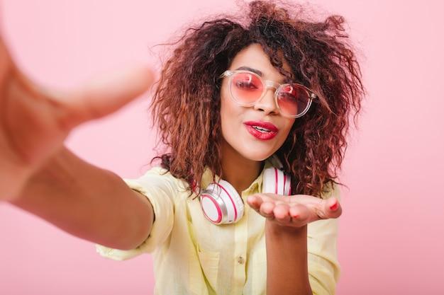 Vrolijke stijlvolle afrikaanse meisje draagt een schattige zonnebril lucht kus verzenden tijdens het maken van selfie thuis. portret van gelukkige mulat dame in geel genieten van goede dag en het nemen van foto van zichzelf. Gratis Foto