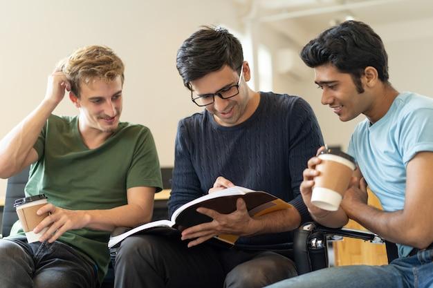 Vrolijke studenten die nota's in werkboek leren Gratis Foto
