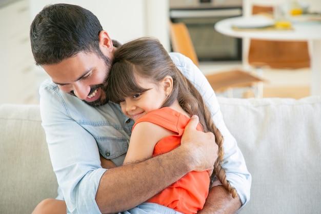 Vrolijke vader zit met zijn kleine meisje op de bank, haar knuffelen en knuffelen. Gratis Foto