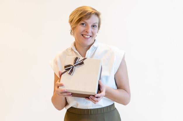 Vrolijke vertrouwen volwassen zakenvrouw geschenk doos te houden Gratis Foto