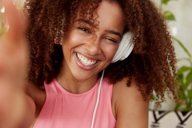 Vrolijke vreugdevolle afrikaanse amerikaanse vrouw poseert voor selfie, heeft een brede glimlach, luistert naar favoriete nummer in de koptelefoon, geniet van recreatietijd, zit in een gezellige cafetaria. mensen en entertainment concept Gratis Foto