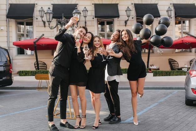 Vrolijke vrienden champagne drinken op feestje buiten Gratis Foto