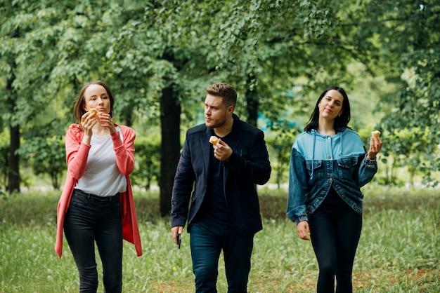 Vrolijke vrienden die in park met roomijs lopen Gratis Foto