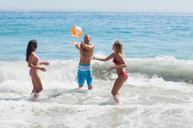 Vrolijke vrienden die met een beachball in het overzees spelen Premium Foto