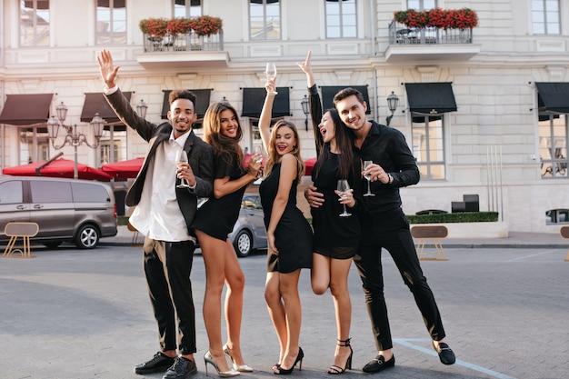 Vrolijke vrienden die plezier hebben tijdens een wandeling door de stad en zwaaiende handen Gratis Foto