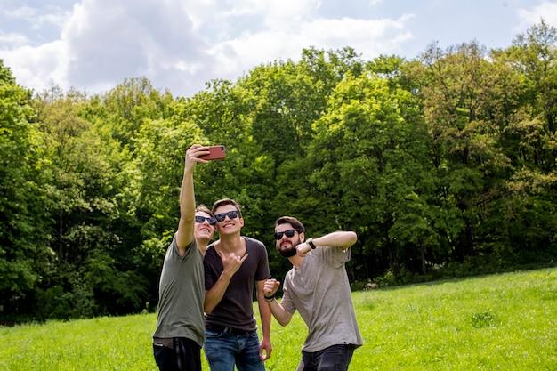 Vrolijke vrienden die selfie op open plek nemen Gratis Foto